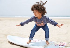 boy trying to surf on sand