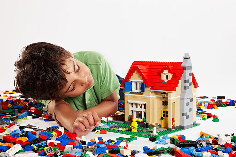 boy building lego house