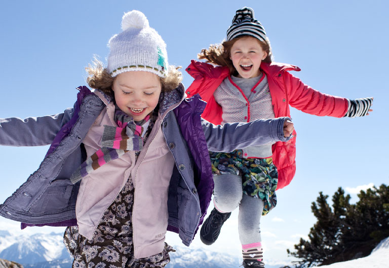 girls jumping in the snow