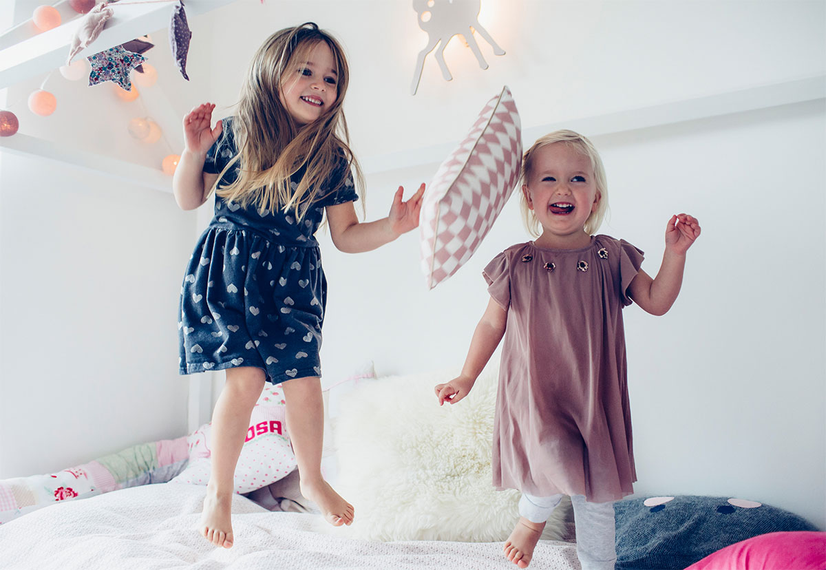sisters jumping on the bed