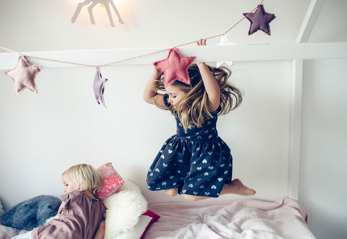 sister jumping on bed